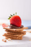 Chocolate sweet melting nougat cream on cookies with strawberries Stock Photography