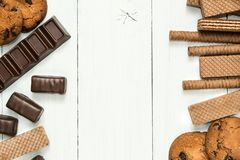 Chocolate sweets, chocolate waffle rolls, cookies on a wooden white table, space in the center for text stock images