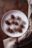 Chocolate sweets with cocoa and coconut chips on a white plate Stock Images