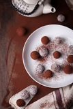 Chocolate sweets with cocoa and coconut chips on a white plate Stock Photos