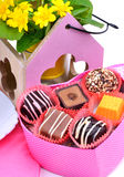 Chocolate sweets in gift boxes, yellow wildflowers Stock Photos