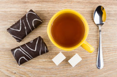 Chocolate swiss rolls, cup of tea, lumpy sugar and teaspoon Stock Image