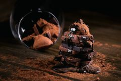 Chocolate syrup dripping on stack of dark and milk chocolate stack, truffles. Sweets in a glass. Chocolate with cocoa powder on dark rustic wooden table royalty free stock image