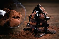 Chocolate syrup dripping on stack of dark and milk chocolate stack, truffles. Sweets in a glass. Chocolate with cocoa powder on dark rustic wooden table royalty free stock photo