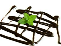 Chocolate syrup and leaf of mint isolated on white Royalty Free Stock Images