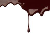 Chocolate syrup leaking liquid sweet food. Close up chocolate syrup leaking on white background Royalty Free Stock Image