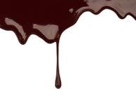 Chocolate syrup leaking liquid sweet food. Close up chocolate syrup leaking on white background Stock Image