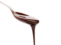 Chocolate syrup leaking from spoon Stock Images