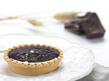 Chocolate tart. A chocolate tart served and decorated with pieces of chocolate and wheat royalty free stock images