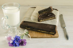Chocolate tart with halva, decorated with cornflowers, near cup of milk Stock Image