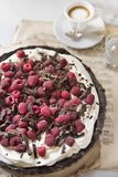 Chocolate tart with raspberries on a vintage background and a cup of fragrant espresso macchiato stock photography