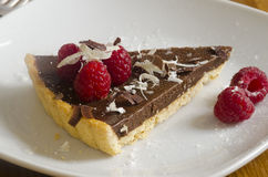 Chocolate tart. Slice of chocolate tart topped with raspberries Royalty Free Stock Image