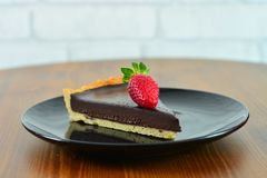 Chocolate tart with strawberry served on black plate. royalty free stock image