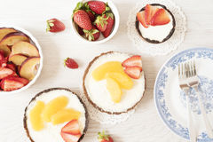 Chocolate tart, tartalette with white chocolate and mascarpone cream, fresh strawberries and orange on top. Gray wooden background Royalty Free Stock Images