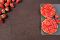 Chocolate tart, tartalette with white chocolate and mascarpone cream, fresh strawberries on top. Border of whole fresh ripe red st Royalty Free Stock Image