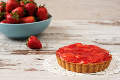 Chocolate tart, tartalette with white chocolate and mascarpone cream, fresh strawberries on top. Large blue bowl full of strawberr Stock Photos