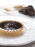 Chocolate tartlet. A chocolate tart served and decorated with pieces of chocolate and wheat royalty free stock photo