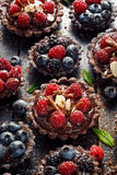 Chocolate tartlets with addition of raspberries, blueberries and blackberries on black table. Delicious chocolate dessert with addition fresh organic raspberries Stock Image