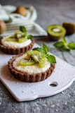 Chocolate tartlets filled with coconut cream and topped with kiwi slices. Delicious chocolate tartlets filled with coconut cream and topped with kiwi slices Royalty Free Stock Images