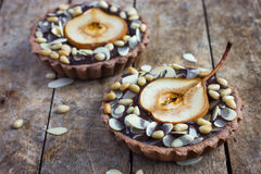 Chocolate tartlets with pear and nuts stock images