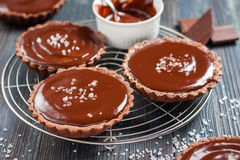 Chocolate tarts with salted caramel. On a dark wooden background in rustic style Stock Photos