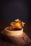 Chocolate tarts with walnut and physalis. On wooden rustic background. Selective focus royalty free stock photos