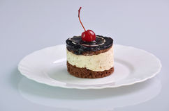 Chocolate tasty cake with cherry. Piece of cake with cherries on a white saucer Stock Photos
