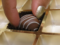 Chocolate temptation. Taking the last chocolate in the box Stock Image