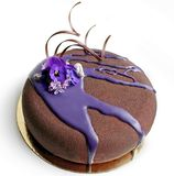 Chocolate textured mousse cake with spring flowers and purple mirror glaze stock photos