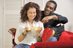 Chocolate Treats. A mixed race couple enjoying chocolates together Royalty Free Stock Image