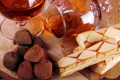 Chocolate truffle and cognac. Chocolate truffle with brandy balloon and pastries puff pastry on pine stump Stock Images