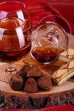 Chocolate truffle and cognac. Chocolate truffle with brandy balloon and pastries puff pastry on pine stump with red cloth background Stock Photos
