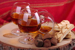 Chocolate truffle and cognac. Chocolate truffle with brandy balloon and pastries puff pastry on pine stump with red cloth background Royalty Free Stock Photos