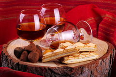 Chocolate truffle and cognac. Chocolate truffle with brandy balloon and pastries puff pastry on pine stump with red cloth background Stock Image