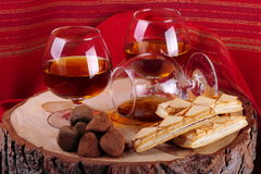Chocolate truffle and cognac. Chocolate truffle with brandy balloon and pastries puff pastry on pine stump with red cloth background Stock Photography