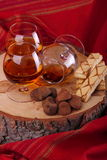 Chocolate truffle and cognac. Chocolate truffle with brandy balloon and pastries puff pastry on pine stump with red cloth background Royalty Free Stock Image