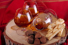 Chocolate truffle and cognac. Chocolate truffle with brandy balloon and pastries puff pastry on pine stump with red cloth background Royalty Free Stock Photography
