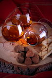 Chocolate truffle and cognac. Chocolate truffle with brandy balloon and pastries puff pastry on pine stump with red cloth background with reflection central Royalty Free Stock Image