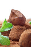 Chocolate truffle with fresh mint. Handmade chocolate truffles with fresh mint dusted with cocoa powder, on white Royalty Free Stock Photography