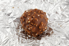 Chocolate truffle on silver wrapper. Chocolate on a silver wrapper Royalty Free Stock Photography
