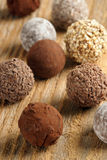 Chocolate truffles. An assortment of chocolate truffles on old wood table. Very Shallow depth of field, focusing on middle truffle stock photo