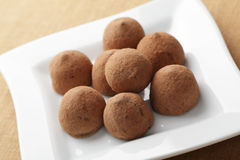 Chocolate truffles. On the white square plate stock images