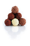 Chocolate truffles. Pyramid of assorted chocolate truffles on white background with reflection stock photo