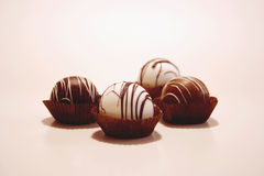 Chocolate Truffles. Four chocolate truffles in paper caps Stock Image