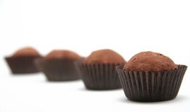 Chocolate truffles. A row of chocolate truffles isolated on a white background Stock Image