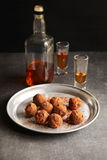 Chocolate truffles on an aluminum plate with 2 glasses of liqueur and a bottle on background Stock Photos