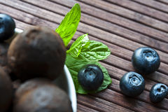 Chocolate truffles with blueberry and mint on wooden background. Chocolate truffles with blueberry and leaf of mint on wooden background Royalty Free Stock Photography
