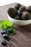 Chocolate truffles with blueberry and mint on wooden background. Chocolate truffles in white porcelain bowl with blueberry and leaf of mint on wooden background Stock Photo
