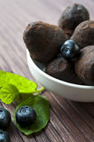 Chocolate truffles with blueberry and mint on wooden background. Chocolate truffles in white porcelain bowl with blueberry and leaf of mint on wooden background Stock Photography