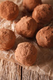 Chocolate truffles close-up on a wooden table. vertical. Chocolate truffles close-up on a wooden table in a rustic style. vertical stock photo